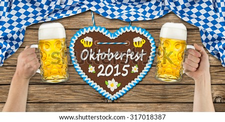 hands holding up beer glasses in front of Oktoberfest gingerbread heart - stock photo