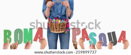 Hands holding up bona pasqua against portrait of a girl holding a basket full of easter eggs - stock photo