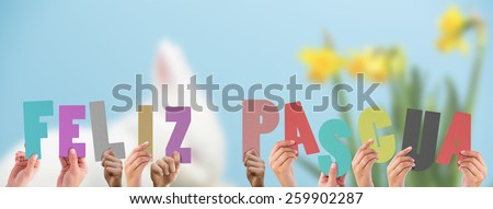 Hands holding up feliz pasqua against white fluffy bunny scratching its nose beside daffodils - stock photo