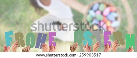 Hands holding up frohe ostern against little girl sitting on grass showing basket of easter eggs to camera - stock photo