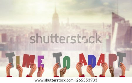 Hands holding up time to adapt against room with large window looking on city - stock photo