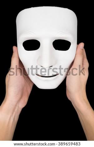 Hands holding white mask on black background. - stock photo