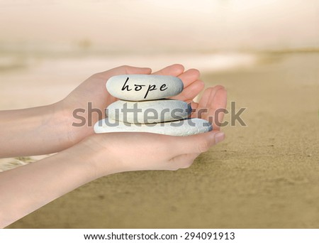 Hands holding white stack of pebbles with 'Hope' written on the top stone. - stock photo