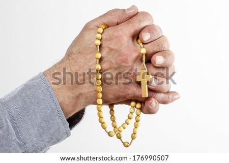 Hands holding wooden rosary - stock photo