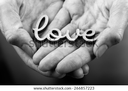 hands holding word love  black on white  - stock photo