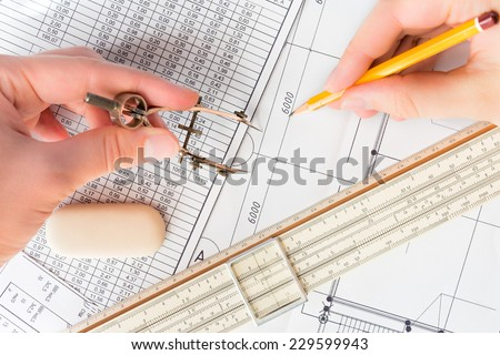Hands holds the pencil and the compass to create a drawing - stock photo