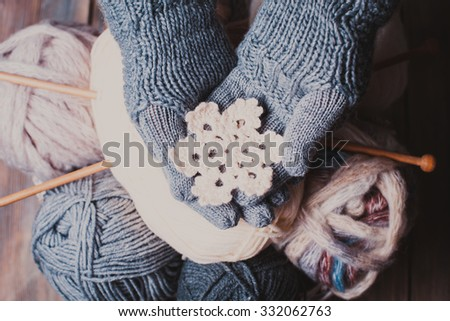 Hands in a grey gloves holding white knitted snowflake as a winter symbol - stock photo