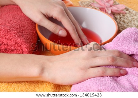 Hands in bowl with cosmetic liquid, closeup - stock photo