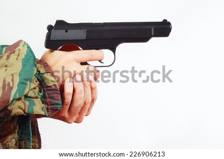 Hands in camouflage uniform with automatic army handgun on a white background - stock photo