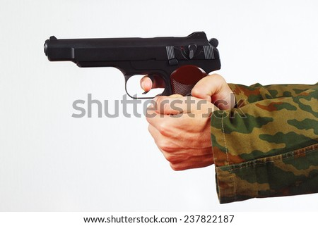 Hands in camouflage uniform with pistol on a white background - stock photo