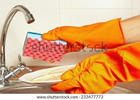 Hands in gloves with dirty dishes over the sink in the kitchen - stock photo