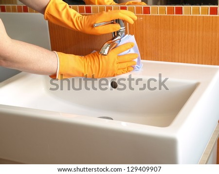 Hands in gloves with rubber cleaning bath faucet - stock photo