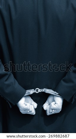 Hands in handcuffs behind back - stock photo