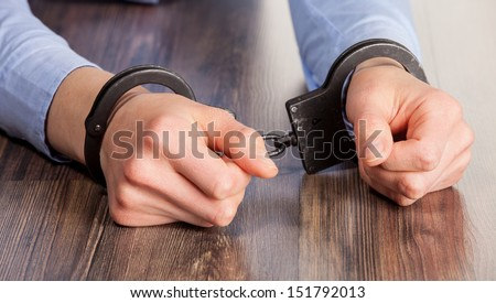 Hands in handcuffs on the table - stock photo