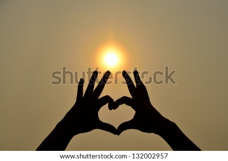 Hands in heart shape with silhouette and shadow with sun in background - stock photo