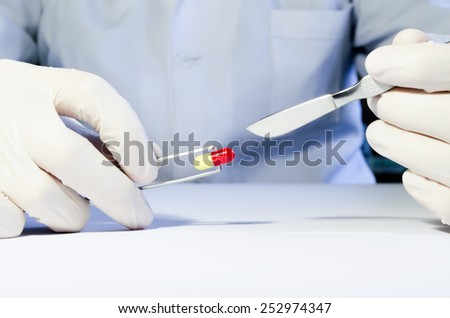Hands in medical rubber gloves holding a scalpel and tweezers with red and yellow capsule. - stock photo