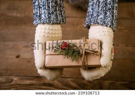 Hands in mittens holding gift box. Woman holding modern Christmas present gift - stock photo