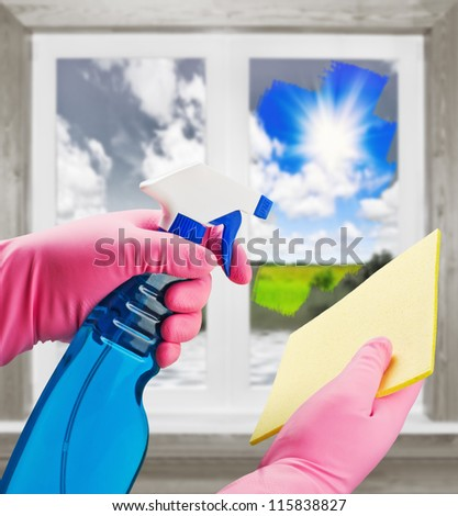 hands in pink gloves with means clears the dirt from the window - stock photo