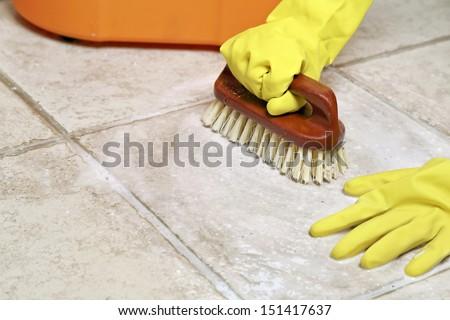 hands in rubber gloves scrubbing the floor - stock photo