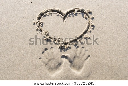Hands in sand with heart shape - stock photo