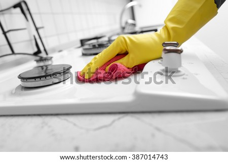 Hands in yellow gloves washing the gas stove. - stock photo