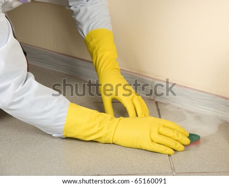 Hands in yellow gloves with sponge, washing floor and plinth - stock photo