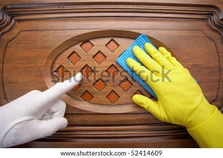 Hands in yellow gloves with sponge, washing wooden surface - stock photo
