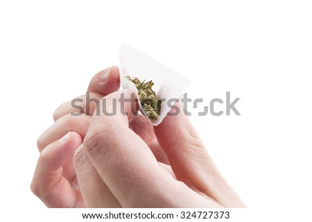 Hands isolated on white background rolling a cannabis joint. Smoking marijuana addiction.  - stock photo