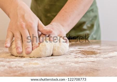 Hands kneading dough - stock photo