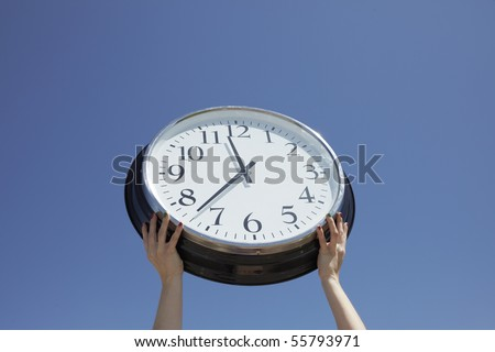 Hands lifting big clock outdoors - stock photo