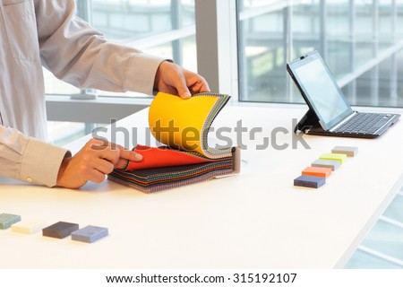 hands looking through color fabric swatches on desk with colored tiles - stock photo