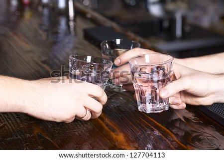 hands make cheers with glasses of vodka - stock photo