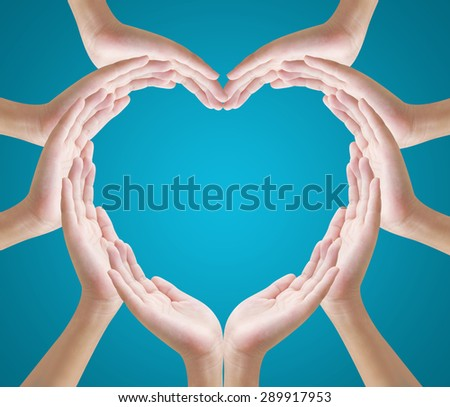 Hands make heart shape on blue ackground - stock photo