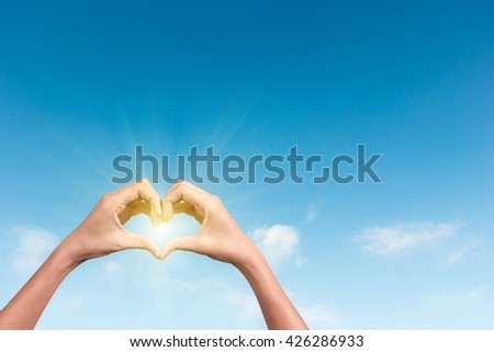 hands making a heart shape in the blue sky with sunlight - stock photo