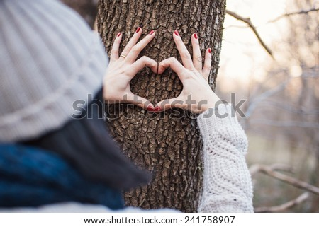 Hands making a heart shape on a tree - stock photo