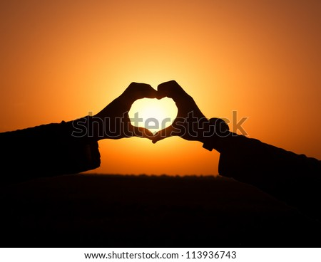 Hands making heart shape with sun in center - stock photo
