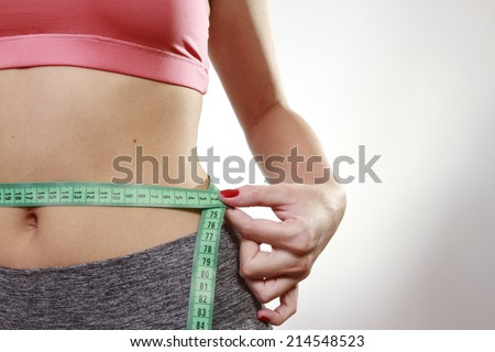 hands measuring with tape the abdomen - stock photo