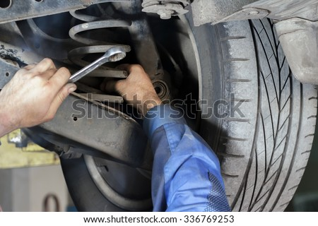 Hands mechanics to repair the suspension on the car - stock photo