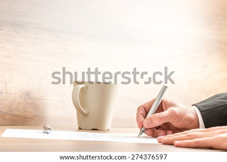 Hands of a businessman writing with a silver pen on a paper sheet, at a wooden desk, next to a mug of coffee or cappuccino, with copy space on blurred beige wall. - stock photo