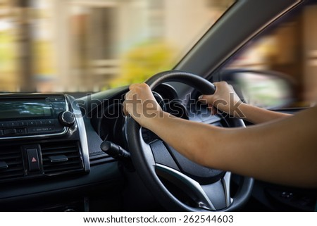 Hands of a driver on steering wheel of a car - stock photo