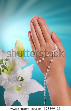 hands of a girl going to the first holy communion prying with rosary on blue background  - stock photo