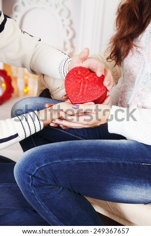 hands of a man and woman holding a heart-shaped box - stock photo