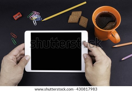 Hands of a man holding blank tablet device over a black workspace table - stock photo