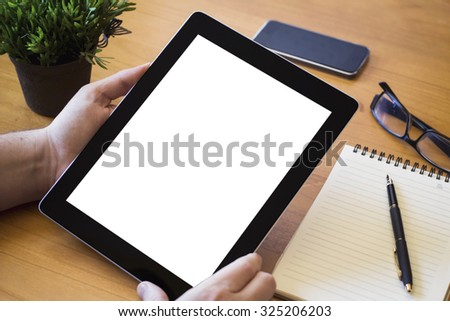 hands of a man holding blank tablet device over a wooden workspace table - stock photo