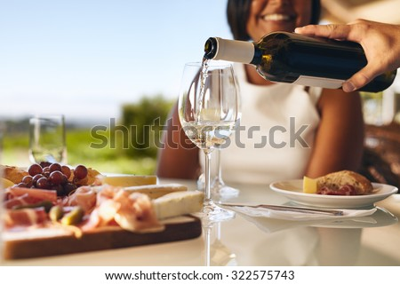 Hands of a man pouring white wine in two glasses from bottle with a woman smiling in background at winery. Focus on glasses and wine bottle. - stock photo