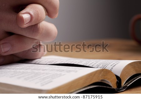 Hands of a man praying over a Bible at his desk. - stock photo