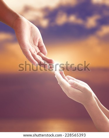 Hands of a man reaching to hand of GOD over blurred sunset. - stock photo