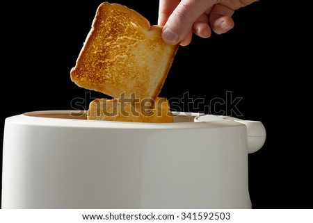 Hands of a man taking fresh toast out of a toaster isolated on black background with clipping path - stock photo