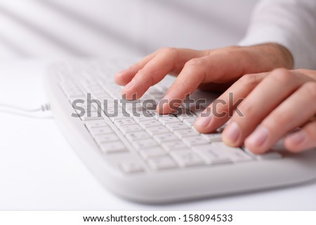 Hands of a man typing on a white computer keyboard as he enters data with shallow dof and copyspace - stock photo