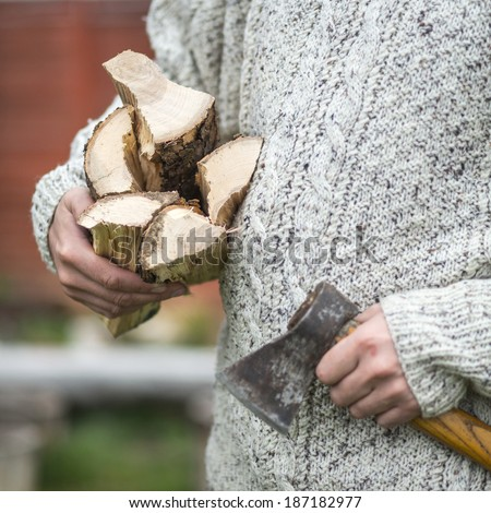 Hands of a man with axe and firewood. focus on wooden logs - stock photo